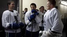 Vancouver Canucks Dan Hamhuis, left to right, Kevin Bieksa and Cory Schneider share a laugh prior to the Bieksa's Buddies charity hockey game at the University of British Columbia in Vancouver, B.C., Wednesday, Oct. 17, 2012. (JONATHAN HAYWARD/THE CANADIAN PRESS)