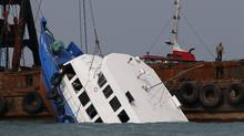 Officials check on a half submerged ferry after it collided near Lamma Island, off the southwestern coast of Hong Kong Island, Oct. 2, 2012. (Vincent Yu/AP)