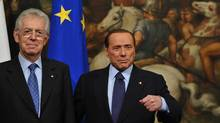 Italy's new Prime Minister Mario Monti, left, poses with outgoing Prime Minister Silvio Berlusconi as Monti takes office on Nov. 16, 2011 at Palazzo Chigi, the Prime Ministry in Rome. (ALBERTO PIZZOLI/ALBERTO PIZZOLI/AFP/GETTY IMAGES)