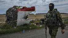 A pro-Russian militiaman walks past part of the aircraft at the site of the Malaysia jet crash near Grabovo, Ukraine, July 20, 2014. (MAURICIO LIMA/NYT)