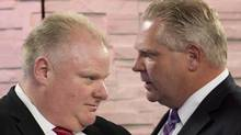 Mayor Rob Ford, left, listens to his brother and campaign manager Doug Ford, right, during a commercial break as Rob Ford takes part in a live television mayoral debate in Toronto on March 26, 2014. (NATHAN DENETTE/THE CANADIAN PRESS)