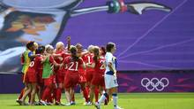 France's Elise Bussaglia (R) walks off the pitch as Canada celebrates winning the women's bronze medal soccer match in Coventry at City of Coventry Stadium at the London 2012 Olympic Games August 9, 2012. (PAUL HACKETT/REUTERS)