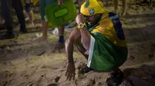 Brazil soccer fan cries after his team lost the World Cup semi-final match against Germany on Copacabana beach in Rio de Janeiro, Brazil, Tuesday, July 8, 2014. (Silvia Izquierdo/AP)