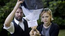 """Swedish Tomas Mazetti, left, and Hannah Frey, right, show a teddy bear on a parachute as they pose for a photo in Berlin, Germany, Wednesday, Aug. 1, 2012. The slogan on the paper fixed to the bear reads """"We support the Belarusian struggle for free speech"""". Mazetti and Frey intruded Belarus' airspace with a Swedish light plane and dropped in hundreds of such teddy bears decked out in parachutes and slogans supporting human rights. (Gero Breloer/AP)"""