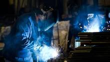 A welder fabricates anchor bolts for roads and bridges at the custom manufacturer Fox Company Inc. in Philadelphia. (MATT ROURKE/AP)