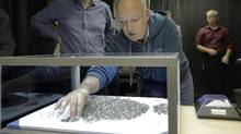 Matt Manson, right, CEO of Stornoway, highlights the differences in rough diamond categories. The diamonds shown represent six days of production at Stornoway's Renard mine in Quebec. (Stornoway Diamond Corp.)