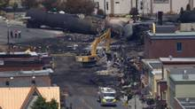 Crews use a backhoe to dig through the rubble of the area where the Musi-Café was located in the centre of Lac-Mégantic, Que., on July 8, 2013. (MOE DOIRON/THE GLOBE AND MAIL)