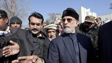 Pakistani-Canadian scholar Tahir-ul-Qadri, right, has emerged as a political wild card in Pakistan whose sudden prominence has sparked queries about his motive and his backers. Mian Kursheed/Reuters