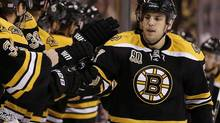 Boston Bruins' Milan Lucic is congratulated at the bench by teamates after a goal against the New Jersey Devils during the first period of an NHL hockey game in Boston, Saturday, Oct. 26, 2013. (Winslow Townson/THE CANADIAN PRESS)