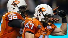 B.C. Lions' Khalif Mitchell, left, and James Yurichuk celebrate after recovering a Calgary Stampeders fumble during the second half of a CFL football game in Vancouver, B.C., on Saturday October 8, 2011. THE CANADIAN PRESS/Darryl Dyck (Darryl Dyck/THE CANADIAN PRESS)