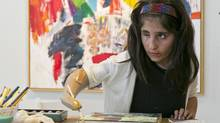 Afghan war victim Shah Bibi Tarakhail uses her new prosthetic arm to paint at Galerie Michael in Beverly Hills, Calif., on April 2, 2014. (DAMIAN DOVARGANES/ASSOCIATED PRESS)