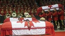 Pallbearers carry the casket of one of three Royal Canadian Mounted Police officers who were killed last week during a regimental funeral in Moncton on June 10.  (Christinne Muschi/Reuters)