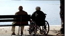 An elderly couple, one in a wheelchair, sit watching the water. (Andreas Kaspar/iStockphoto)