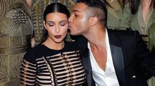 Fashion designer Olivier Rousteing kisses Kim Kardashian as they pose prior to attending the Vogue party, in Paris, Wednesday July 9, 2014. (Thibault Camus/AP)