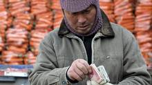 A man counts money in front of a truck loaded with carrots at a wholesale market in Fuyang in central China's Anhui province. (AP/AP)
