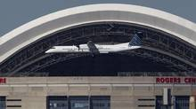 A Porter turboprop plane passes the Rogers Centre as it approaches the island airport. (MOE DOIRON/THE GLOBE AND MAIL)