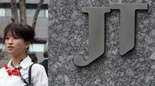 A woman walks past the Japan Tobacco Inc. (JT) headquarters in Tokyo. The Japanese government's $7.7-billion stake sale in Japan Tobacco was one of the three largest equity offerings in the world in the first quarter of 2013. (TOSHIYUKI AIZAWA/REUTERS)
