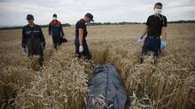 """Members of the Ukrainian Emergency Ministry prepare to remove a body at the crash site of Malaysia Airlines Flight MH17, near the settlement of Grabovo in the Donetsk region July 19, 2014. Ukraine accused Russia and pro-Moscow rebels on Saturday of destroying evidence of """"international crimes"""" from the wreckage of the Malaysian airliner that Kiev says militants shot down with a missile, killing nearly 300 people (Maxim Zmeyev/REUTERS)"""