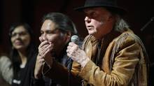 """Singer Neil Young, right, makes a point as he speaks during a news conference before the last concert in his """"Honour the Treaties"""" tour in Calgary, Sunday, Jan. 19, 2014. (Jeff McIntosh/THE CANADIAN PRESS)"""