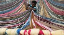 A boy separates starched sarees left to dry on the roof of a cotton factory in the southern Indian city of Hyderabad in a file photo. (KRISHNENDU HALDER/REUTERS)
