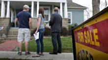 Denny Reichard, an agent with Jim Maloof Realtors, right, stands with potential home buyers Brian Giebelhausen and Lindsay Willing outside a previously owned home in Mackinaw, Ill. (Daniel Acker/Bloomberg)