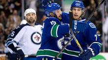 Vancouver Canucks' Brad Richardson, centre, and David Booth, right, celebrate Richardson's goal as Winnipeg Jets' Mark Stuart, left, looks on during first period NHL hockey action in Vancouver, B.C., on Sunday December 22, 2013. (DARRYL DYCK/THE CANADIAN PRESS)