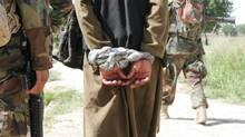 A man Afghan authorities suspect of insurgency-related activities is interrogated during a joint Canadian-Afghan army patrol in the Panjwaii District of Kandahar province on Thursday, July 2, 2009. (COLIN PERKEL/Colin Perkel/The Canadian Press)
