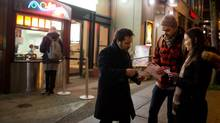 Ben Ratner, left, director and writer of the film Down River, his wife, actor Jennifer Spence, right, one of the stars of the film, and producer James Brown hand out cards and pens to promote the film outside Fifth Avenue Cinemas in Vancouver on Tuesday, March 4, 2014. (DARRYL DYCK For The Globe and Mail)