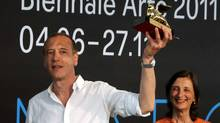 "Christian Marclay holds up the Golden Lion for for the best artist at the ILLUMInations Exhibition section at ""La Biennale di Venezia"" in Venice, Italy, on Saturday. (Luigi Costantini/AP)"