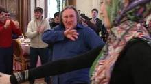 In this Sunday, Feb. 24, 2013 frame grab made from the Associated Press video French actor Gerard Depardieu, center, dances during a reseption, in Chechnya's provincial capital Grozny, Russia. (Associated Press)