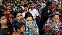 People look at a burnt garment factory outside Dhaka, Bangladesh, Sunday, Nov. 25, 2012. At least 112 people were killed late Saturday night in a fire that raced through the multi-story garment factory just outside of Bangladesh's capital, an official said Sunday. (Hasan Raza/AP)