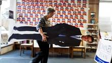Volunteer Clare Frew puts away a cut-out of Mitt Romney at a Republican campaign office in Savannah, Ga. (Stephen Morton/Associated Press)