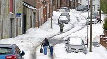 People walk through heavy snow as wintry weather continues to cause havoc across the United Kingdom, in north Belfast March 25, 2013. Thousands of people in Scotland and Northern Ireland were still without power on Monday after snow and high winds brought down electricity lines in some of the worst March weather for half a century. (CATHAL MCNAUGHTON/Reuters)