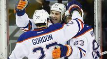 Edmonton Oilers' Ryan Smyth, centre, celebrates his goal with teammates Boyd Gordon, left, and Ales Hemsky, from the Czech Republic, during first period NHL hockey action against the Edmonton Oilers in Calgary, Alta., Friday, Dec. 27, 2013. (JEFF MCINTOSH/THE CANADIAN PRESS)