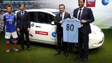 "Nissan president and CEO Carlos Ghosn (second from the right) holds a Manchester City jersey with Manchester City CEO Ferran Soriano, right, as they pose with Akira Kaetsu, president of the Yokohama F Marinos and player Manabu Saito in Yokohama, Japan. Nissan will become a sponsor of City Football Group. The ""80"" on the soccer jersey refers to Nissan's 80 years in business. (YUYA SHINO/REUTERS)"