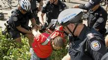 A protester is arrested by police after a demonstration in Toronto on Monday. (Kevin van Paassen/The Globe and Mail)