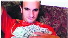 Accused conman Simon Gann poses covered in U.S. $100 bills in this undated handout photo.