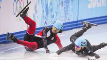 Canadian Charles Hamelin slips and cashes taking out American Eduardo Alvarez during the men's 1000m quarter finals event February 15, 2014 at the Sochi Winter Olympics. (John Lehmann/The Globe and Mail)