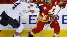 Edmonton Oilers' Sheldon Souray, left, shoves Calgary Flames' Jarome Iginla during first period NHL hockey action in Calgary on Saturday Jan. 30, 2010. THE CANADIAN PRESS/Larry MacDougal (Larry MacDougal)
