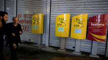 People make their way past mailboxes outside a closed Hellenic Post branch in Athens, Greece, on March 20, 2017. (ALKIS KONSTANTINIDIS/REUTERS)