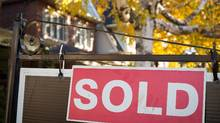 A real-estate sold sign hangs in front of a west-end Toronto property. (Graeme Roy/The Canadian Press)