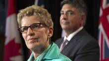 Ontario Premier Kathleen Wynne and Finance Minister Charles Sousa appear at a press conference following the passing of the provincial budget at Queen's Park June 11, 2013. (Moe Doiron/The Globe and Mail)
