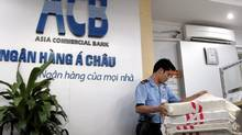 A security officer carries a bag of money into the vault at Asia Commercial Bank's Hanoi branch on Thursday, after the arrest of the bank's director general sparked more panic among depositors. (Hau Dinh/AP)