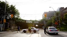 Police constables stand at the corner of King Street at Atlantic Avenue, which remains closed after flooding from rain shut down the underpass, leaving raw sewage and a possible water main break in Toronto on July 9, 2013. (Deborah Baic/The Globe and Mail)