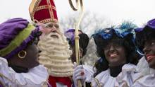 The Dutch version of Santa Claus, Sinterklaas, is shown with his sidekicks, known as Black Pete, in Hoorn on Nov. 16, 2013. (PETER DEJONG/ASSOCIATED PRESS)