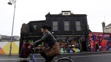 A woman cycles past the Coffee To Get Her restaurant near Dublin city centre which becomes a bar and club in the evenings October 8, 2012. (CATHAL MCNAUGHTON/REUTERS)