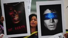 A woman holds placards outside the courthouse ahead of the third day of the trial of Dr. Conrad Murray on September 29, 2011 in Los Angeles. (FREDERIC J. BROWN/AFP/Getty Images)