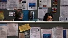 Job seekers look at ads at a jobs fair in Toronto in late March (Fernando Morales/The Globe and Mail)