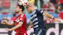 Toronto FC forward Gilberto, left, heads the ball with Sporting Kansas City midfielder Victor Munoz, right, during first half MLS soccer action in Toronto on Saturday, July 26. (Nathan Denette/THE CANADIAN PRESS)