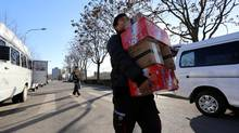 Workers for Chinese e-grocer SF Best load vans with product for delivery near Beijing's Olympic park. The fast-growing Chinese e-commerce market will soon eclipse the U.S. online shopping market. (Nathan VanderKlippe/The Globe and Mail)